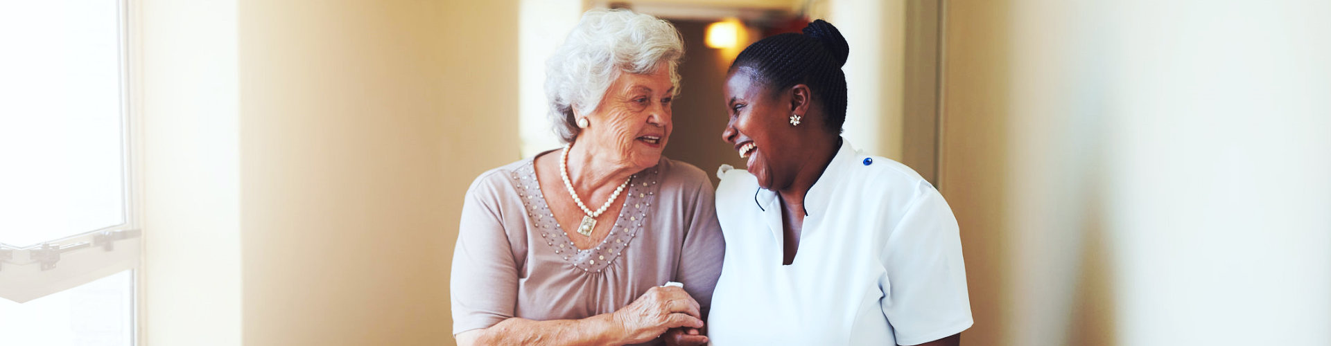 staff and elderly woman smiling to each other