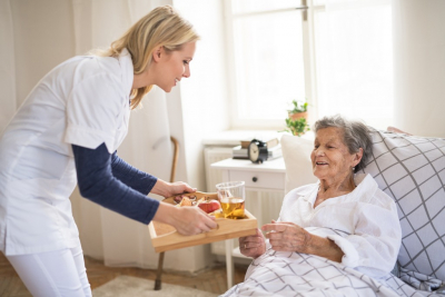 caregiver offering senior woman breakfast